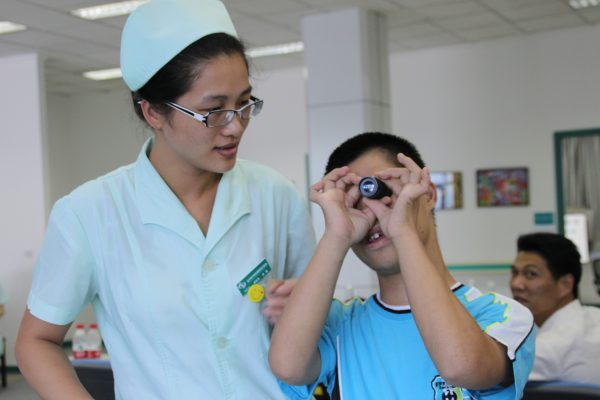Staff nurse instructs patient in use of a telescopic device at the Wenzhou Medical College's new Center of Excellence in Low Vision (Wenzhou, China): a partnership program with the SUNY College of Optometry