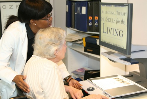 Vision rehabilitation therapist helping elderly woman learn to use screen magnifier