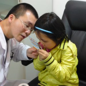 Staff doctor examining a child with low vision at the Wenzhou Medical College's new Center of Excellence in Low Vision (Wenzhou, China): a partnership program with the SUNY College of Optometry