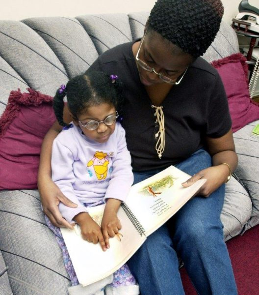 Visually impaired child reading braille book with mother