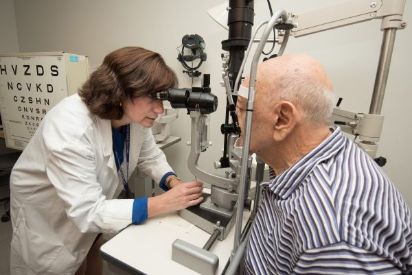 Ophthalmologist carrying out low vision exam on elderly man