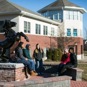 5 students gathering next to statue of a horse