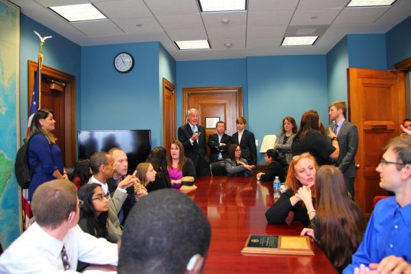 Young adults speaking with politicians in conference room
