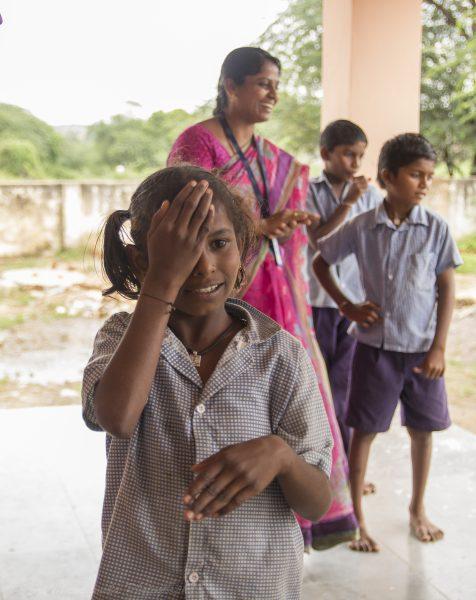 Little girl covering eye for eye exam