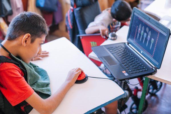 Boy sitting at desk using computer